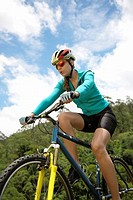 Young woman riding mountain bike, low angle view