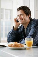 Mid adult man talking on the phone at breakfast table