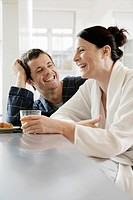 Mid adult couple laughing at breakfast table