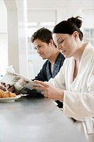 Mid adult couple reading newspaper at breakfast