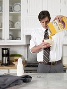 Businessman pouring cereals in bowl