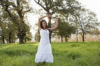 Teenage girl in white dress in field