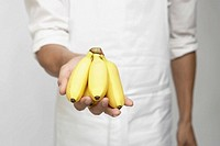 Chef holding bunch of bananas mid section