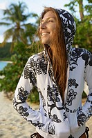 Mid adult woman in hooded top on beach