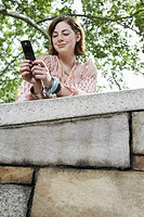 Teenage girl using mobile phone low angle view