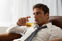 Mid adult businessman drinking white wine on armchair