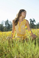 Young woman with eyes closed sitting in a field of wildflowers low angle view