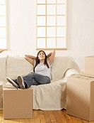 Mid_Adult Woman Resting by Cardboard Boxes