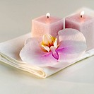 Lighted candles with a colorful orchid