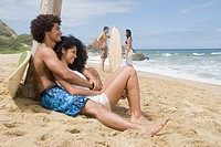 People relaxing at beach with surfboards
