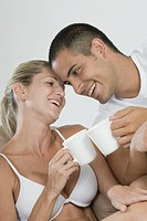 Hispanic couple toasting coffee cups