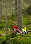Girl with red hat reading in forest
