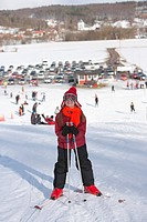 Girl with red cap and orange scarf is skiing