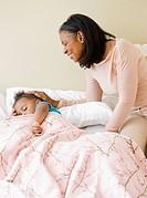 African grandmother checking on sleeping granddaughter