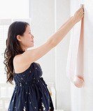 Pregnant Asian woman decorating room with wallpaper
