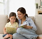 Mother reading story book to daughter