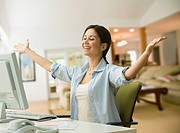 Cheering woman smiling at computer
