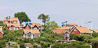 Red houses with Swedish flags in archipelago, Karlskrona, Blekinge, Sweden