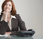 Attractive businesswoman with phone at desk