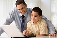 Hispanic father watches as son uses laptop