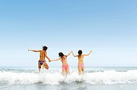 Three girls jumping over wave