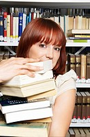 Young woman carrying pile of books (thumbnail)