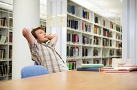 Young man working in library (thumbnail)