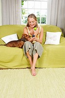 Young woman with dog on couch (thumbnail)