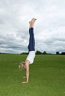 Woman in park doing handstand (thumbnail)