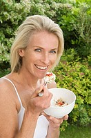 Woman eating fruit and muesli