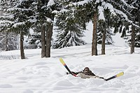 Woman lying in the snow with skis