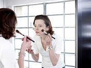 Woman in mirror applying make up