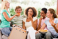 Group Of Teenagers Sitting On A Couch Eating Pizza