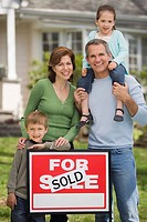 Family in front of house with For Sale/Sold sign