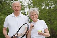 Portrait of mature couple with tennis racquets