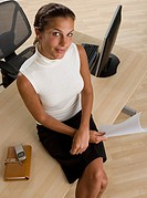 High angle view of businesswoman sitting on desk
