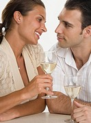 Couple smiling at each other and drinking wine