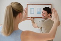 Couple hanging picture on wall