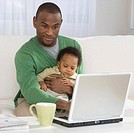 Father holding baby and typing on laptop