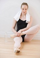 Female ballet dancer stretching on floor