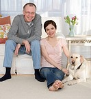 Portrait of couple with dog in livingroom