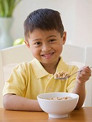 Asian boy eating cereal