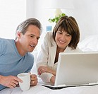 Couple looking at laptop on bed