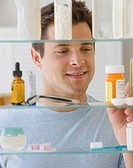 Man looking in medicine cabinet