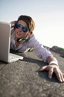 Man with laptop, wearing sun glasses, lying on belly, portrait