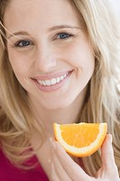 Close up of woman holding orange wedge