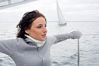 Germany, Baltic Sea, Lübecker Bucht, Young woman standing on yacht, arms outstreched, portrait