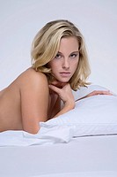 Blonde woman lying on bed, portrait