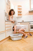 Couple, man kneeling down with his head in a washing machine