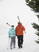 Couple walking with skis over shoulders
